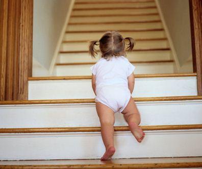 Малыш в возрасте 15 месяцев поднимается по лестнице